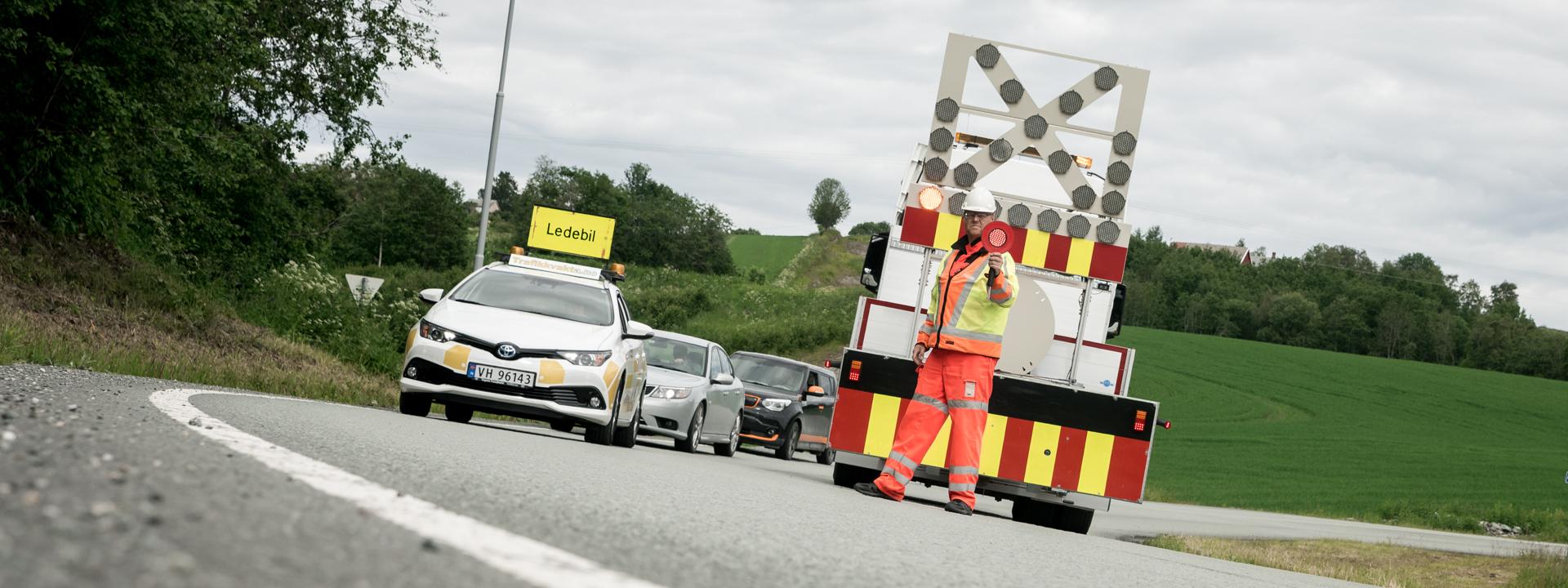 Arbeidsvarsling - Ledebil leder trafikken mens vår trafikkdirigent stopper motgående trafikk.